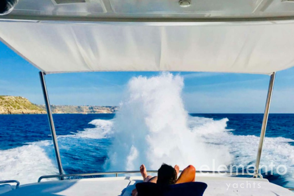 Yacht Charter in Majorca: Pershing 76 cruising, sunbed area aft deck.