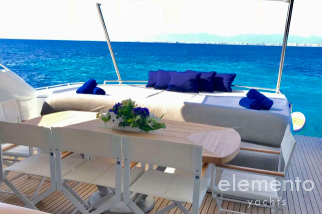 Yacht Charter in Majorca: Pershing 76 table and sunbed area at the aft deck.