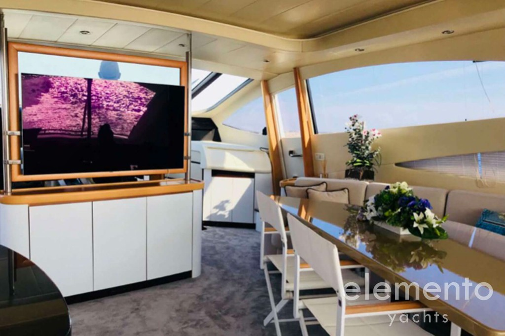 Yacht Charter in Majorca: Pershing 76 awesome salon with table and tv.