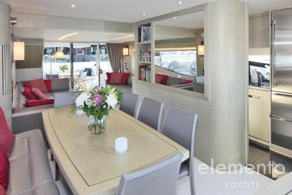 Yacht Charter in Majorca: Sunseeker 75 dining table and galley in the salon.