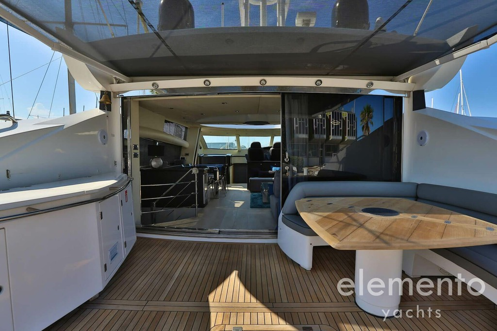 Yacht Charter in Majorca: Sunseeker Predator 82 aft deck with table and entrance to the salon.