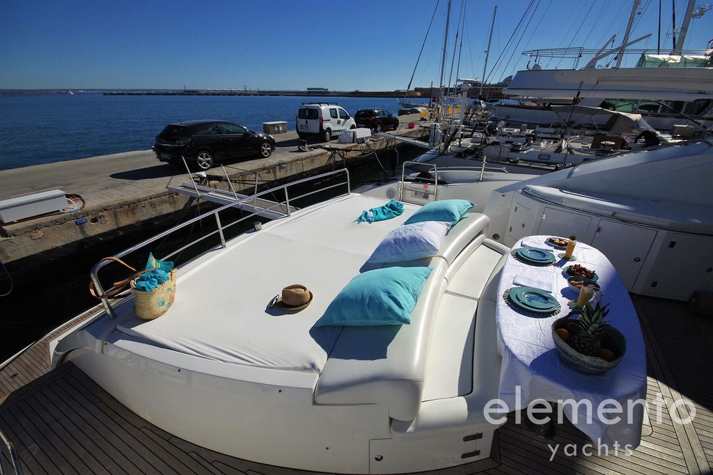 Yacht Charter in Majorca: Sunseeker Predator 82 aft deck with dining table.