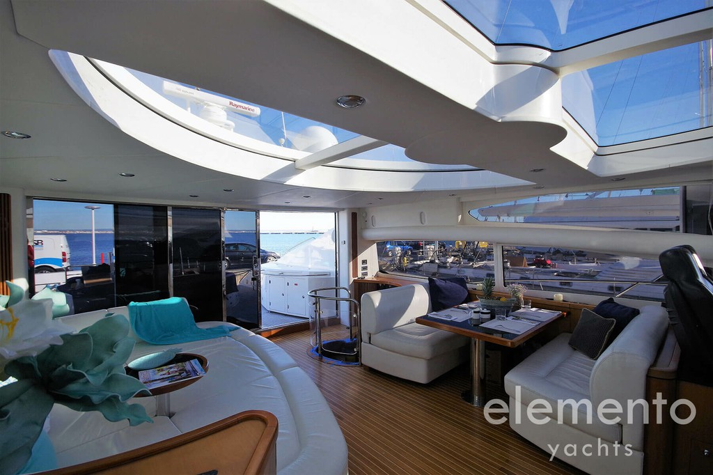 Yacht Charter in Majorca: Sunseeker Predator 82 salon with sofa and dining table.